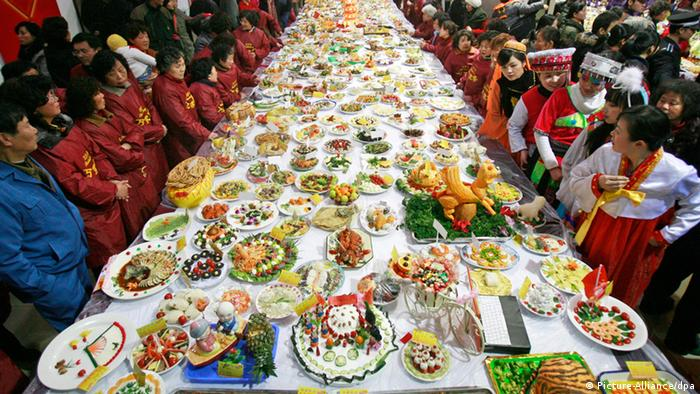Asiatische Menschen in Festkleidung stehen an einem riesigen Tisch mit vielen Speisen