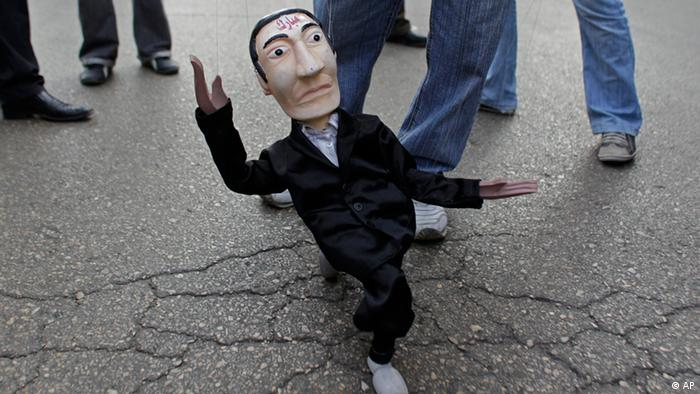 A puppet representing former Egyptian President Hosni Mubarak is carried by a man as he arrives to Tahrir square for Friday prayers followed by a demonstration in Cairo, Egypt, Friday Feb. 18, 2011. Protests continued and labor unrest has increased in Egypt since President Hosni Mubarak's departure last week that set off a chain reaction around the Middle East, with anti-government demonstrations reported in Libya, Bahrain and Yemen.(AP Photo/Ben Curtis)
