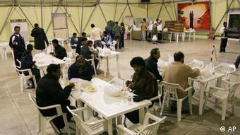 A view of a meal being served to would -be immigrants coming from Rosarno, in southern Italy's Calabria region, in the CARA (reception center for asylum seekers) in Bari (in southern Italy's Puglia region) after they abandoned their make-shift accomodations set up in former industrial sites in Rosarno, Tuesday, Jan. 12, 2010. U.N. human rights officials said Tuesday that they were deeply worried about Italy's deep-rooted racism against migrants following clashes in a southern town between African farmworkers, residents and police. Hundreds of Africans fled the farm town of Rosarno in the underdeveloped southern region of Calabria in trains, cars and caravans of buses arranged by authorities after two days of violence last week that erupted when two migrants were shot with a pellet gun in an attack they blamed on racism. (AP Photo/Donato Fasano)