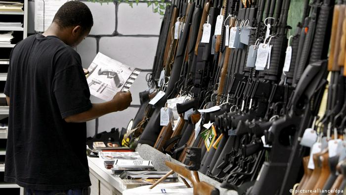 A man looks at a wall display of rifles in a gun shop