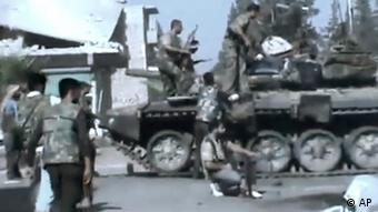 In this image made from amateur video released by the Ugarit News and accessed Monday, July 23, 2012, Free Syrian Army soldiers sit on a military tank during clashes with Syrian government troops in Aleppo, Syria. The Syrian regime acknowledged for the first time Monday that it possessed stockpiles of chemical and biological weapons and said it will only use them in case of a foreign attack and never internally against its own citizens. (Foto:Ugarit News via AP video/AP/dapd) TV OUT, THE ASSOCIATED PRESS CANNOT INDEPENDENTLY VERIFY THE CONTENT, DATE, LOCATION OR AUTHENTICITY OF THIS MATERIAL