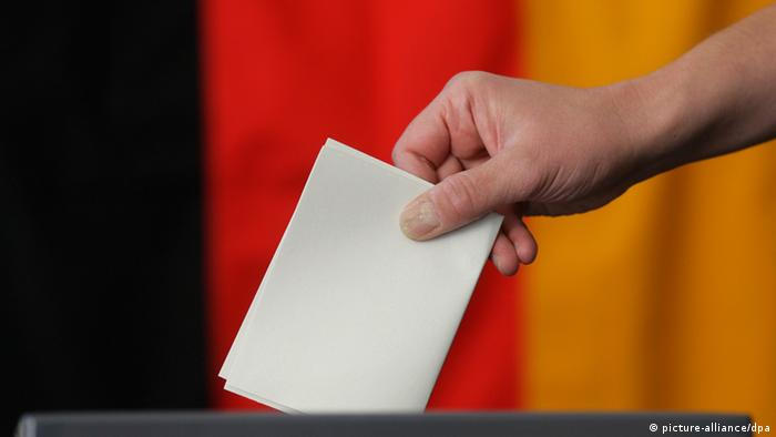 A hand putting a voting slip into a ballot box before a German flag