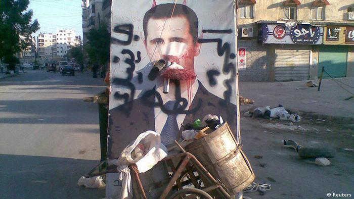 Source News Feed: EMEA Picture Service ,Germany Picture Service A defaced poster of Syria's President Bashar al-Assad is seen near garbage containers in Aleppo July 24, 2012. The words on the poster read, We coming, duck ass. Picture taken July 24, 2012. REUTERS/Shaam News Network/Handout (SYRIA - Tags: POLITICS CIVIL UNREST) FOR EDITORIAL USE ONLY. NOT FOR SALE FOR MARKETING OR ADVERTISING CAMPAIGNS. THIS IMAGE HAS BEEN SUPPLIED BY A THIRD PARTY. IT IS DISTRIBUTED, EXACTLY AS RECEIVED BY REUTERS, AS A SERVICE TO CLIENTS