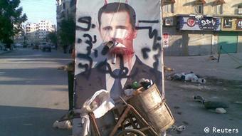 A defaced poster of Syria's President Bashar al-Assad