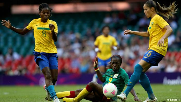 Cameroon's Madeleine Ngono Mani (C) falls in between Brazil's Formiga (L) and Erika during their women's Group E football match at the London 2012 Olympic Games in the Millennium Stadium in Cardiff July 25, 2012. REUTERS/Francois Lenoir (BRITAIN - Tags: SPORT SOCCER SPORT OLYMPICS)
