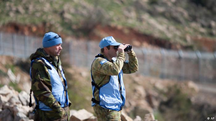 UN officers, one using binoculars, look towards Syria as they stand along the border between Majdal Shams in the Golan Heights, and Syria, as security is tightened ahead of Land Day,Friday, March 30, 2012. March 30 is traditionally marked by Israeli Arabs as Land Day, a time of protests against the confiscation of Arab-owned lands by Israel. In recent years, Palestinians have joined in. (Foto:Ariel Schalit/AP/dapd)