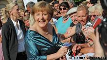 German Chancellor Angela Merkel (CDU) signs autographs upon her arrival at the opening of the Bayreuth Festival 2012 in Bayreuth, Germany, 25 July 2012. The one-month festival is Germany's most prestigious culture event. Photo: Marc Mueller dpa/lby/ef pixel