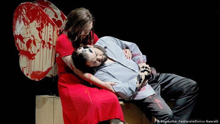 Ariane Pieczonka als Senta und Samuel Youn als Holländer sitzen auf der Bank. Senta trägt ein blutendes Herz wie Engelsflügel
