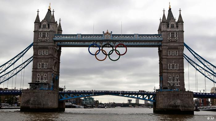 The Olympic rings are seen atop the iconic Tower Bridge in London, after they were lowered into position, coinciding with one month to go until the start of London 2012 Games, Wednesday, June 27, 2012. The giant rings, which are fully retractable to allow for tall ships to pass through the bridge, will remain in position for the duration of the Games. (Foto:Lefteris Pitarakis/AP/dapd)