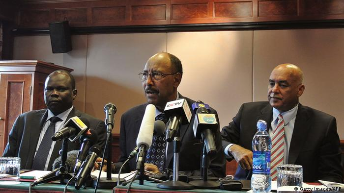 South Sudan's chief negotiator, Pagan Amum (L) sits alongside Sudan's Defence Minister Abdel-Rahim Mohamed Hussein (C), Sudanese spokesman Omer Dahab (R) as they announce that both countries have agreed to improve ties and cease hostilities during the latest round of talks in Addis Ababa on July 7, 2012. Sudan and South Sudan pledged to cease hostilities along their disputed oil-rich border Saturday but stopped short of actually signing an agreement, officials said. The verbal agreement came as the latest round of talks closed in the Ethiopian capital ahead of celebrations Monday to mark one year of independence for South Sudan.Negotiations resumed in May following weeks of deadly clashes along the oil-rich disputed border in April which brought the two rivals back to the brink of all-out war. The United Nations passed a resolution in May urging both sides to resolve outstanding disputes on oil sharing revenue and border demarcation by August 2. AFP PHOTO/JENNY VAUGHAN (Photo credit should read JENNY VAUGHAN/AFP/GettyImages)