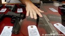 ARCHIV - Der Verkäufer eines Waffengeschäftes in Wichita, Kansas, USA, greift am 26.06.2008 in einer Auslage nach einer Pistole. Nach der blutigen Schießerei in Aurora ist das Waffenrecht in den USA wieder in der Diskussion. Foto: Larry W. Smith dpa (zu dpa Experte: Für viele Amerikaner sind Waffen Teil ihrer Identität vom 23.07.2012) +++(c) dpa - Bildfunk+++
