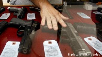 A hand hovers over a selection of guns. Foto: Larry W. Smith dpa