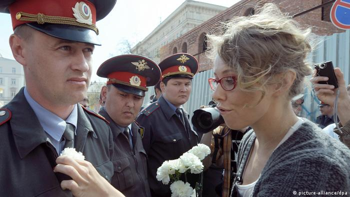 Ksenia Sobchak gives white flowers to policemen during opposition protests (picture-alliance/dpa)