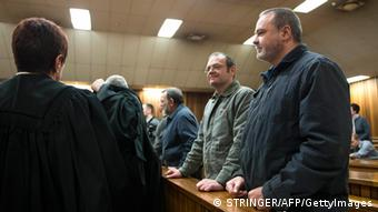 This photo taken on July 25, 2012, shows accused Mike du Toit (R) and his brother Andre du Toit (L) standing in the courtroom at the Pretoria Hight Court. The 'Boeremag' trial (Afrikaans for Boer Force) of 20 rightwingers accused of high treason, terrorism and possession of weapons and explosives has been billed as one of the longest and most expensive in South Africa. On July 23, the Pretoria High Courg began delivering a judgement. On October 30, 2002, nine bomb blasts shook Soweto in the early hours of the morning, killing a woman and injuring her husband. The bombings were said to be aimed at creating instability and panic to allow the group to unseat the ruling African National Congress (ANC) and chase blacks and Indians from the country. AFP PHOTO / STRINGER (Photo credit should read STRINGER/AFP/GettyImages)
