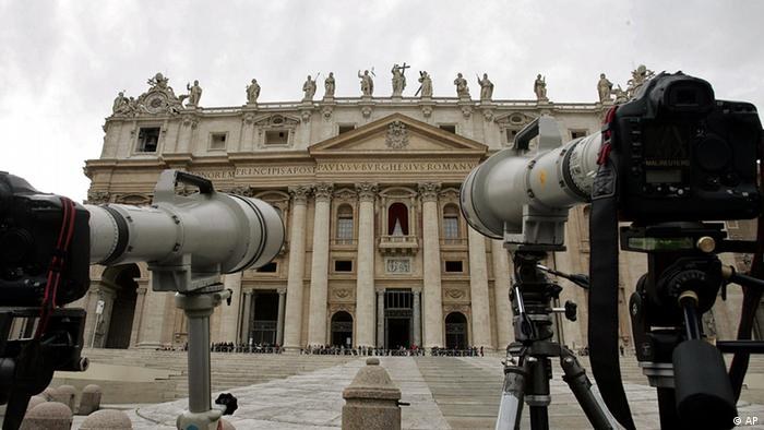 Cameras with long lenses are pointed at the balcony, centre, where the newly elected pope will appear after his election by 115 voting cardinals, in St. Peter's Square at the Vatican, Monday April 18, 2005. Representing 52 countries, the 115 crimson-robed princes sequestered themselves in the Sistine Chapel to start deliberating their choice of new pope. (AP Photo/Luca Bruno)