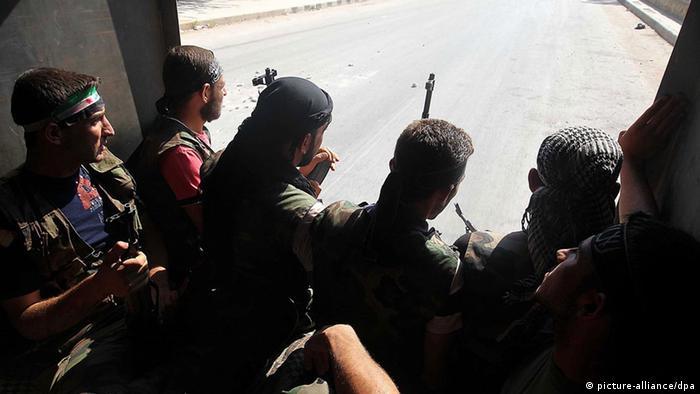 Syrian rebels patrol near Aleppo, Syria, 26 July 2012.