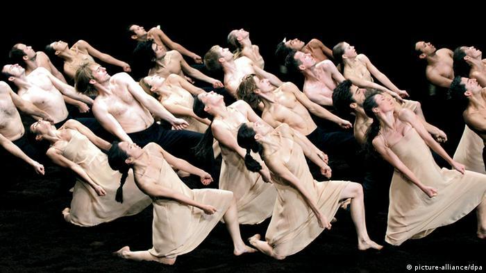 Tänzer und Tänzerinnen in beiger Kleidung knien auf einer schwarzen Bühne und verbiegen sich.  (c) ANNE-CHRISTINE POUJOULAT/AFP/Getty Images