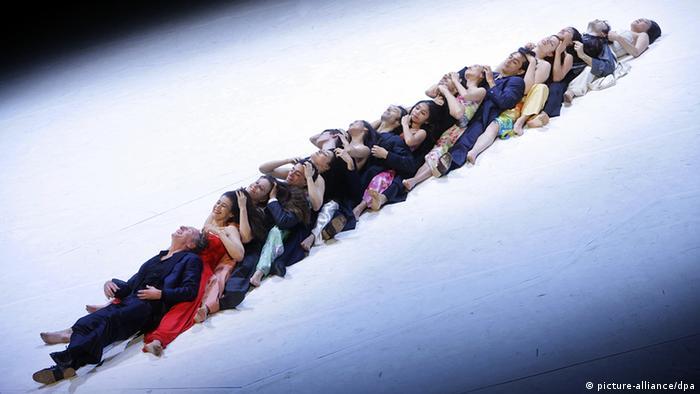 Tänzer sitzen hintereinander und ineinander verschränkt auf der Bühne und bilden eine Linie. (c) dpa - Bildfunk