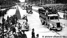 Adolf Hitler grüßt im offenen Wagen stehend die vorbeifahrenden Bauarbeiter. Am 19. Mai 1935 wurde im Beisein einer riesigen Zuschauermenge das erste Teilstück der Reichsautobahn Frankfurt-Heidelberg durch Reichskanzler Adolf Hitler übergeben. Mit den Bauarbeiten an den Straßen des Führers war am 23. September 1933 begonnen worden. Das Projekt Reichsautobahn diente neben der Verbesserung der Infrastruktur des Straßenverkehrs der Arbeitsbeschaffung und somit der Ankurbelung der Wirtschaft. Auch militärstrategische Gesichtspunkte spielten für den raschen Ausbau der innerdeutschen Verkehrswege eine große Rolle.