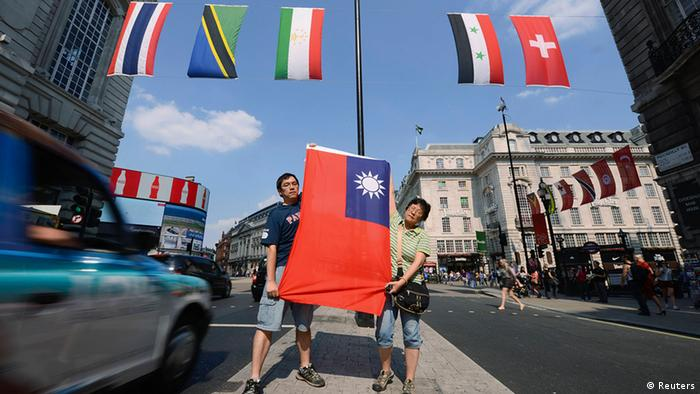 Two Taiwanese citizens hold up the flag of Taiwan (C) at the retail district of Lower Regents Street in London July 25, 2012. The International Olympic Committee decided in 1980 that Taiwan could only compete under the title Chinese Taipei and use a flag designed after the ruling.    REUTERS/ Ki Price (BRITAIN  - Tags: SPORT OLYMPICS POLITICS)