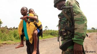 Soldier looks at a man and boy in the Democratic Republic of Congo (DRC).