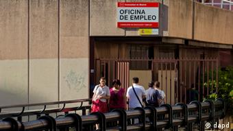 People leave as others arrive at an unemployment registry office in Madrid, Friday, July 27, 2012.