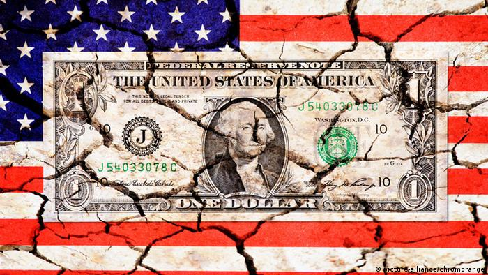 An American flag is shown with a dollar bill in the middle, both with cracks superimposed on them (c) picture-alliance/chromorange