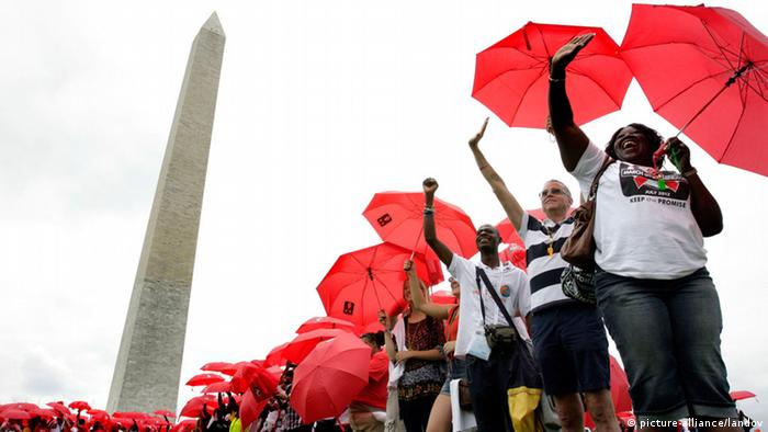 Hundreds of people form a red ribbon with umbrellas as part of the Keep the Promise on HIV/AIDS rally in Washington on July 22