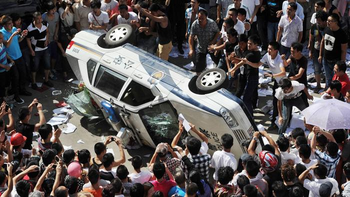 Protesters in Qidong push over a police vehicle