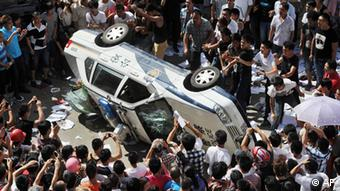 Local residents push over a police vehicle as they gather to protest against plans for a water discharge project in Qidong, China (c) Kyodo News/AP/dapd