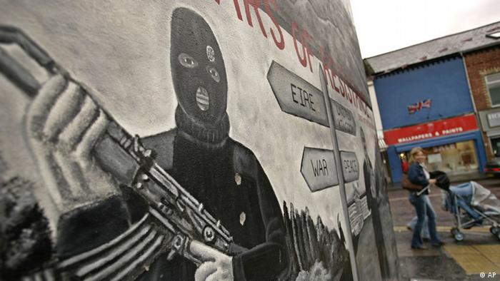 People walk past a mural in the largely Protestant area of the Shankill Road area of Belfast, Northern Ireland, Monday Sept. 26, 2005. Disarmament officials presented a confidential report Monday to the British and Irish governments detailing the Irish Republican Army's recent secret handover of its weapons stockpiles, a long-elusive goal of Northern Ireland peacemaking. (ddp images/AP Photo/Lefteris Pitarakis)