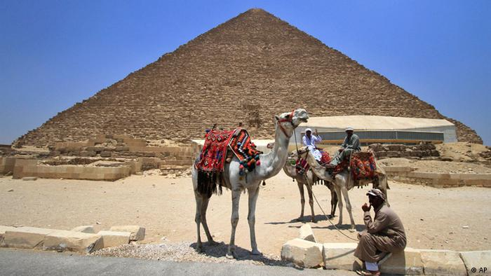 Tourists guides sit on camels as they wait for clients next to the Giza pyramids on the outskirts of Cairo, Egypt, Thursday, June 23, 2011. (ddp images/AP Photo/Khalil Hamra)