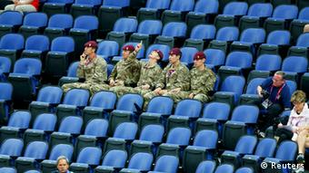 Soldiers sit in the empty seats held by the IOC as they watch the women's gymnastics qualification in the North Greenwich Arena during the London 2012 Olympic Games July 29, 2012. REUTERS/Mike Blake