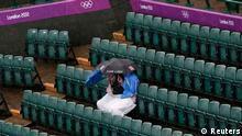Spectators huddle under umbrellas as they wait out the rain at the All England Lawn Tennis Club during the London 2012 Olympic Games July 29, 2012. REUTERS/Adrees Latif (BRITAIN - Tags: SPORT TENNIS OLYMPICS TPX IMAGES OF THE DAY)