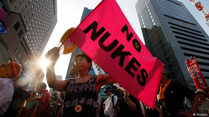 An anti-nuclear protester holds a flag reading: No Nukes during a demonstration in Tokyo July 29, 2012. (Photo: REUTERS/Yuriko Nakao)