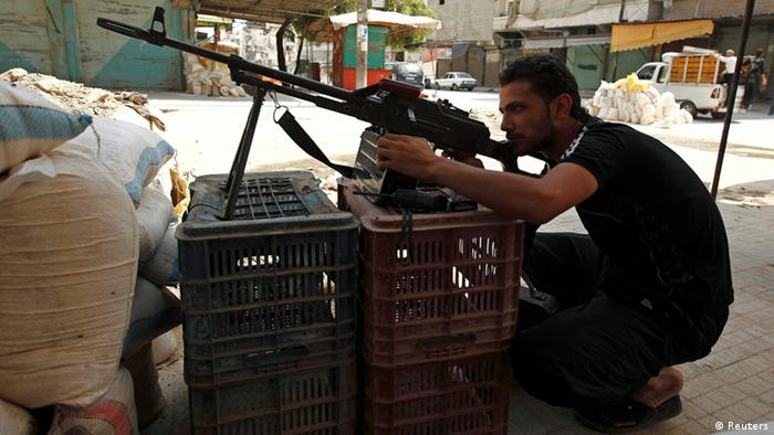 Rebel propping up gun on plastic crates in Aleppo