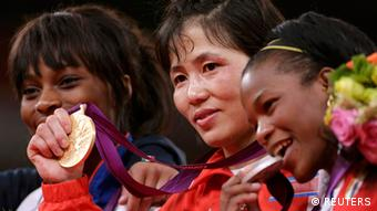 North Korea's An Kum Ae celebrates her gold medal victory next to silver medallist, Cuba's Yanet Bermoy Acosta (R) and bronze medallist France's Priscilla Gneto (L) during the awards ceremony for the women's 52kg judo competition at the London 2012 Olympic Games July 29, 2012.