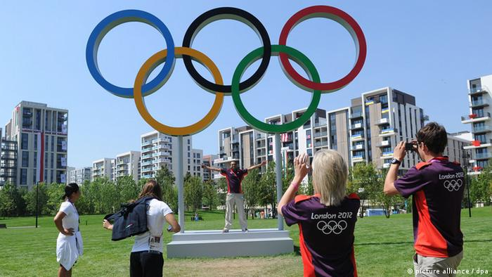 1191834 Great Britain, London. 07/26/2012 Athletes are photographed against the backdrop of the Olympic rings in the Olympic village in London. Alexey Kudenko/RIA Novosti