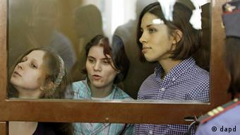 Feminist punk group Pussy Riot sit behind bars at a court room in Moscow, Russia