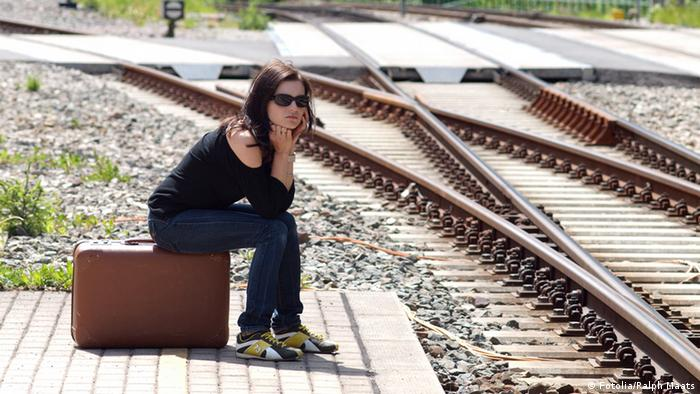 A young woman sits on her suitcase and waits for the next train.