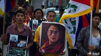 Tibetan exiles carry Tibetan flags and a portrait of the Dalai Lama