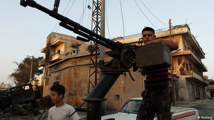 A Free Syrian Army member stands by his anti-aircraft machine gun