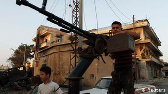 A Free Syrian Army member stands by his anti-aircraft machine gun during their patrol in Attarib, on the outskirts of Aleppo province July 30, 2012. REUTERS/Zohra Bensemra (SYRIA - Tags: POLITICS CONFLICT CIVIL UNREST)