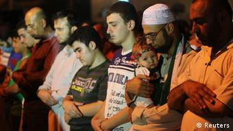 Syrian refugees and residents perform night prayers during the holy month of Ramadan before a protest in front of the Syrian Embassy in Amman July 26, 2012.
