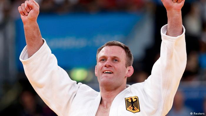 Germany's Ole Bischof celebrates after defeating Italy's Antonio Ciano (blue) in their men's -81kg elimination round of 32 judo match, at the London 2012 Olympic Games July 31, 2012.