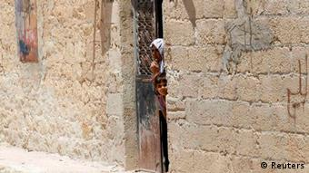 A Syrian woman and a girl look out from a house in Azaz, northern Syria, July 25, 2012.