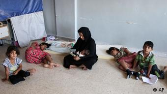 A Syrian refugee who identified herself as Um Ali sits with her children inside a government school in Marj, Lebanon