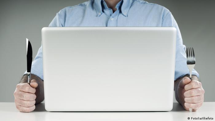 Молодой человек за компьютером со столовыми приборами в руках