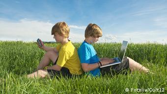 Дети за компьютом на лужайке