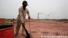 Smoke emits from chimney as a Bangladeshi worker puts coal at the fire place of a brick field at Amin Bazar, outskirts of Dhaka, Bangladesh, Thursday, May 14, 2009. The World Bank approved on Wednesday a US$62.2 million credit to help Bangladesh to control urban air pollution through cutting emissions in key polluting sectors such as transport and brick-making according to news reports. (ddp images/AP Photo/Pavel Rahman)